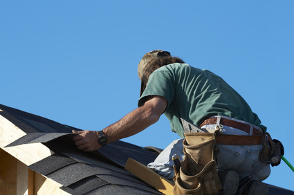 worker on roof putting shingles down
