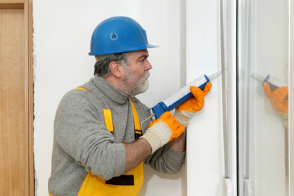 Home renovation, worker caulking with silicone door, window